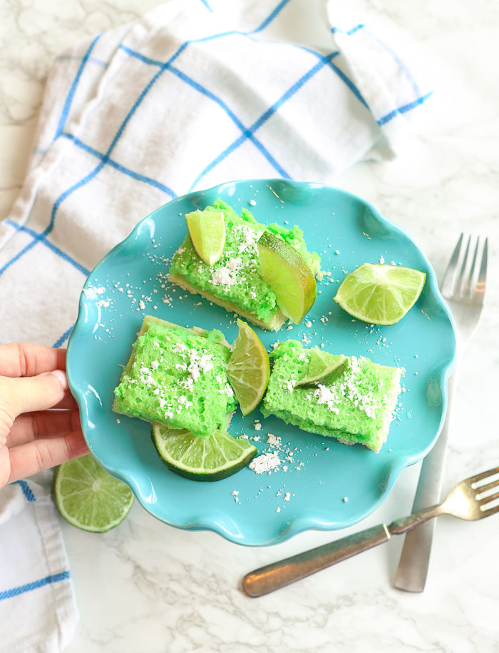 green gluten-free lime bars on a blue platter with powdered sugar and lime slices