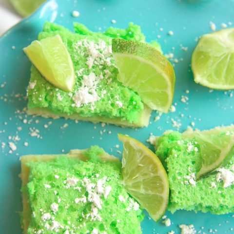 vertical close up of green gluten-free lime bars on a blue platter with powdered sugar and lime slices