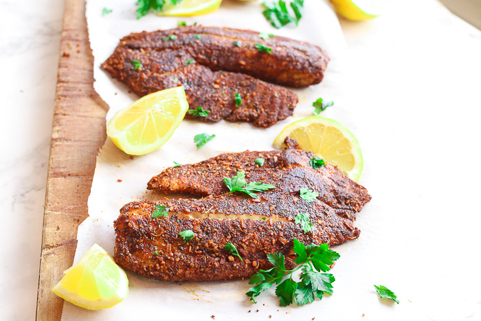 blackened flounder on paper with lemon slices