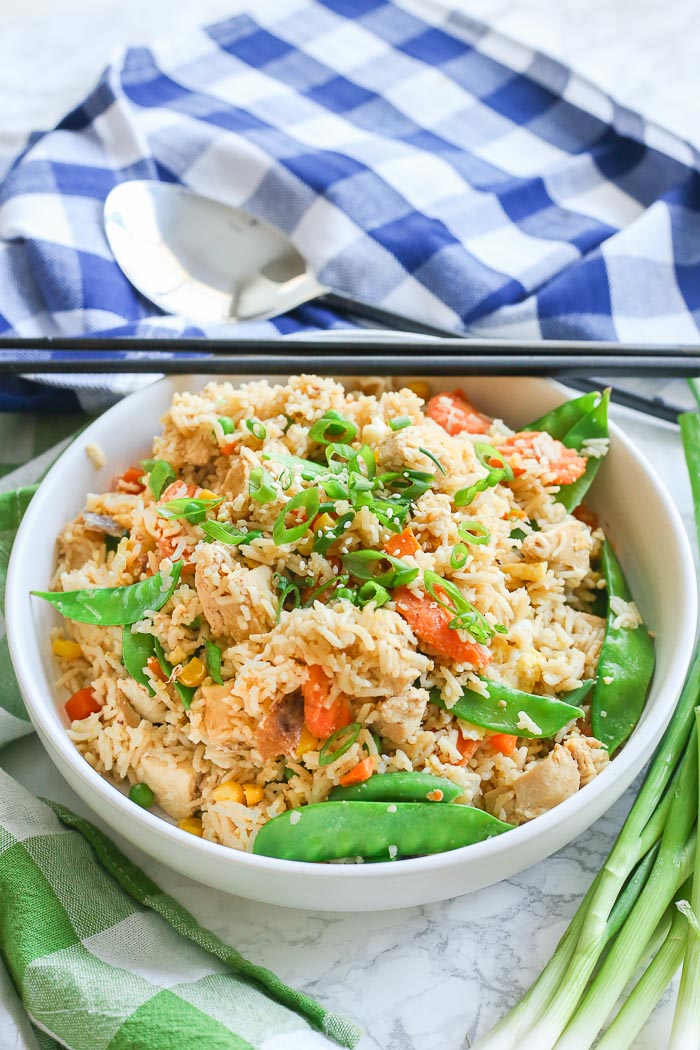 fried rice with chicken and peas in white bowl