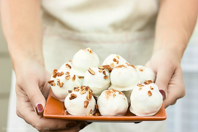 These pumpkin pecan truffles have smooth creamy pumpkin centers with pecan pieces hidden inside. The white chocolate coating is drizzled overtop and more pecan pieces sprinkled for the finale. Perfect no-bake party treats that can be quickly made! www.blessherheartyall.com