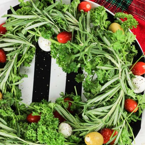 This holiday vegetable wreath is a festive holiday appetizer that is not only easy to put together, put easily adaptable to the party-goers likes and needs. Plate your favorite herbs underneath tasty mozzarella cheese, sweet tomatoes, and your favorite olives. Sprinkle cracked pepper and a delicious balsamic drizzle to finish!