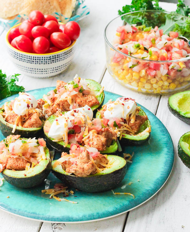 These chicken taco avocado boats are a quick and tasty option for your party or appetizer table. These are a healthy alternative to tacos while keeping that punch of flavor! www.BlessHerHeartYall.com