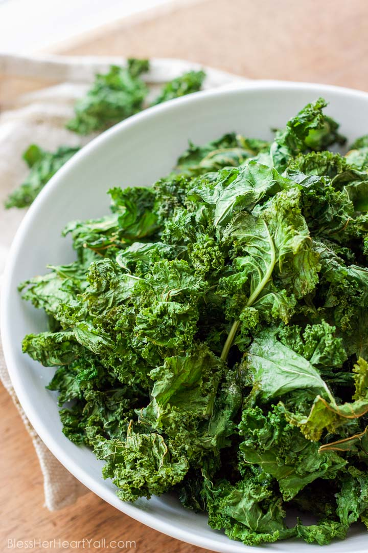 These easy Garlic Kale Chips are just as tasty as store bought chips, are just as inexpensive, and can be made in just minutes! www.BlessHerHeartYall.com