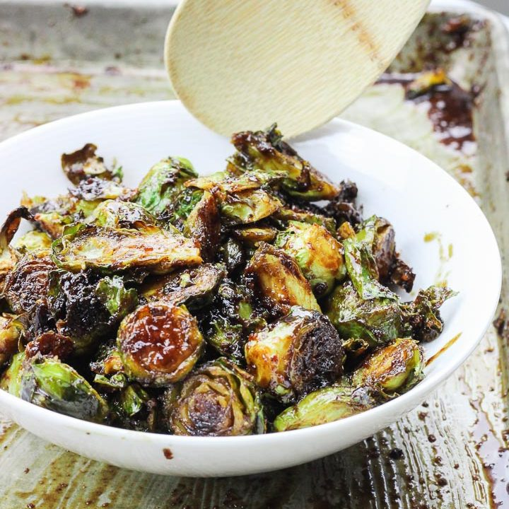 These roasted bacon walnut brussel sprouts are an easy side dish full of sweet hearty flavors! The sprouts are roasted in lemon juice and olive oil before being drizzled with a bacon walnut reduction and then quickly roasted again! www.BlessHerHeartYall.com