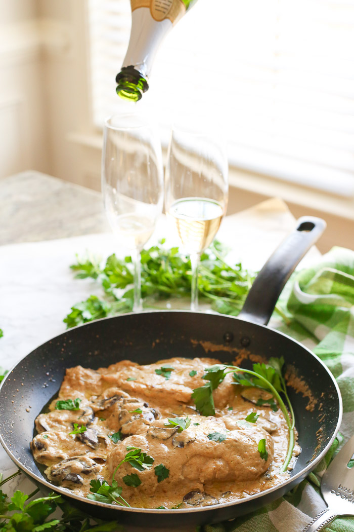champagne chicken with mushrooms cooked in skillet pouring champagne in flutes behind food