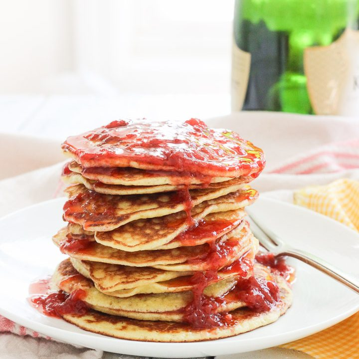 These gluten-free pancakes with smashed strawberry sauce recipe is one for the books! The pancakes are light and fluffy (and yes, I promise are gluten-free!) with a touch of coconut's sweetness. The smashed strawberry champagne sauce is a fun topper, with strawberries, lemon juice, and champagne caught up together in a thick, warm syrupy sauce to smother your pancakes in! Breakfast is now the best meal of the day! | BlessHerHeartYall.com |