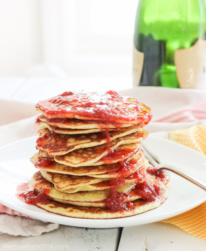 These gluten-free pancakes with smashed strawberry sauce recipe is one for the books! The pancakes are light and fluffy (and yes, I promise are gluten-free!) with a touch of coconut's sweetness. The smashed strawberry champagne sauce is a fun topper, with strawberries, lemon juice, and champagne caught up together in a thick, warm syrupy sauce to smother your pancakes in! Breakfast is now the best meal of the day!   BlessHerHeartYall.com  