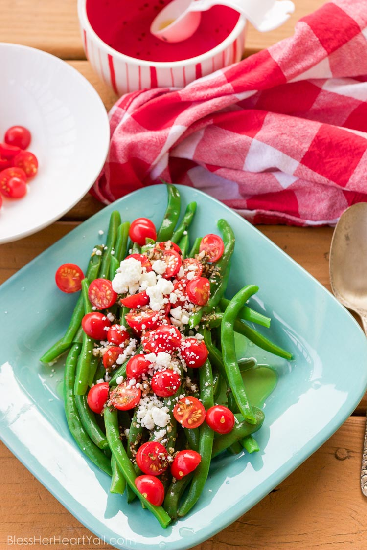 These 5 minute greek green beans use fresh cooked green beans that are drizzled with a quick homemade greek dressing and topped with fresh tomato and feta cheese crumbles. They are great served warm or cold and are perfect for all those summer parties!