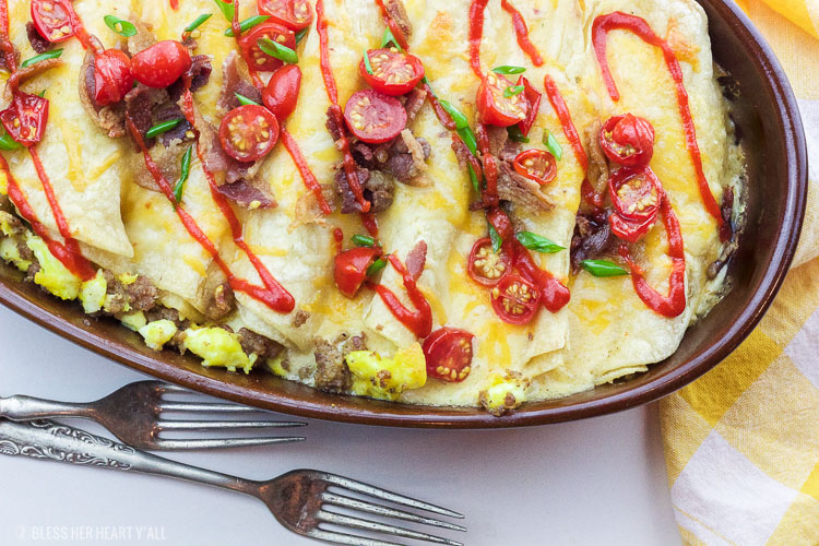 This delicious recipe for gluten-free breakfast enchiladas will wake anyone's taste buds up for the day! The combination of fluffy eggs and spicy breakfast sausage wrapped in corn tortillas and then topped with a seasoned cheese drizzle, baked and then loaded with fresh veggie chunks and bacon crumbles will make anyone's morning sunny!
