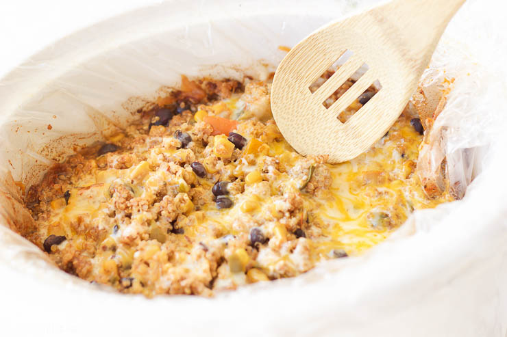 This slow cooker mexican quinoa dip is the perfect gluten-free, vegetarian, and paleo friendly tailgating comfort food! It's warm and gooey, filling and nutritious, and cooks itself in the slow cooker for a quick 2-3 hours. Use this recipe as a dip with your favorite sweet potato chips, rolled up in a tortilla for a quick enchilada, or toss it over a salad to add a burst of flavor!