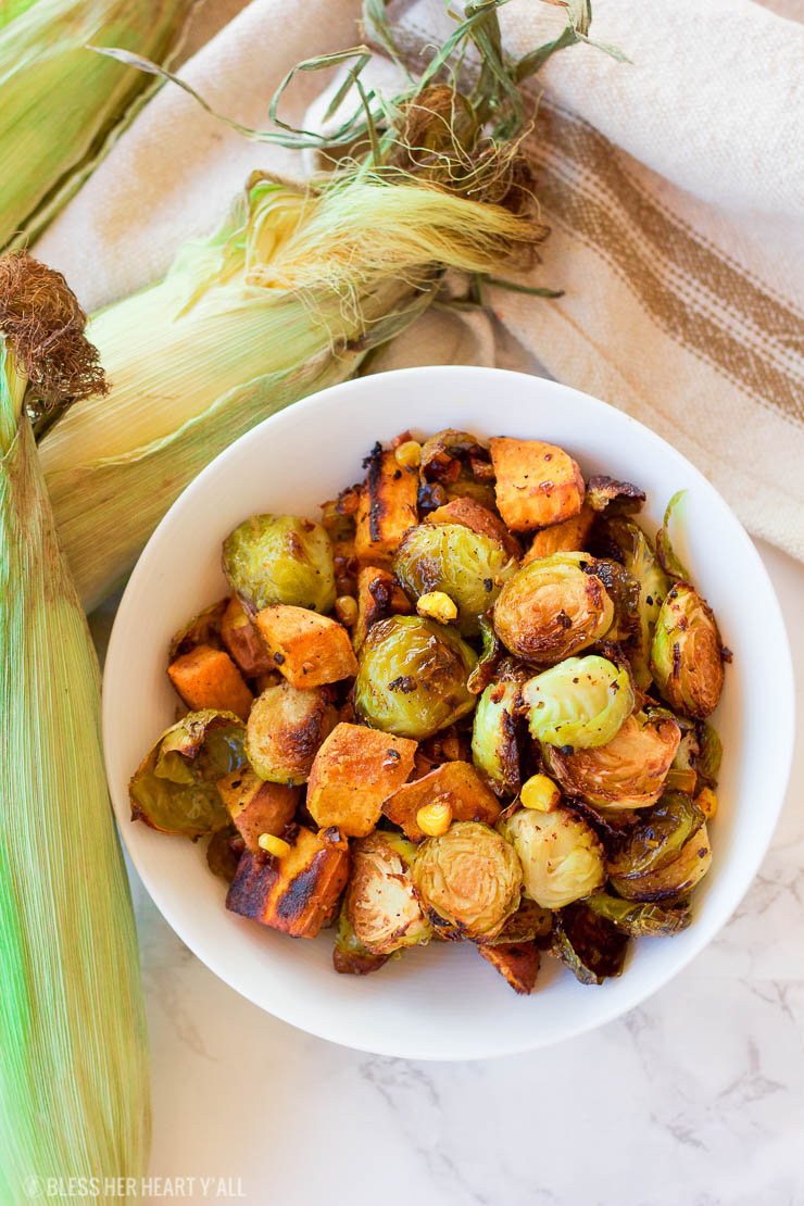This healthy roasted sweet potato brussel sprout hash is a simple fall treat that drizzles on a light layer of olive oil, garlic, and cumin before roasting. The vegan and gluten-free recipe produces perfectly golden baked sweet potato pieces surrounded by fresh spiced corn kernels and crisp and tender cooked brussel sprouts.