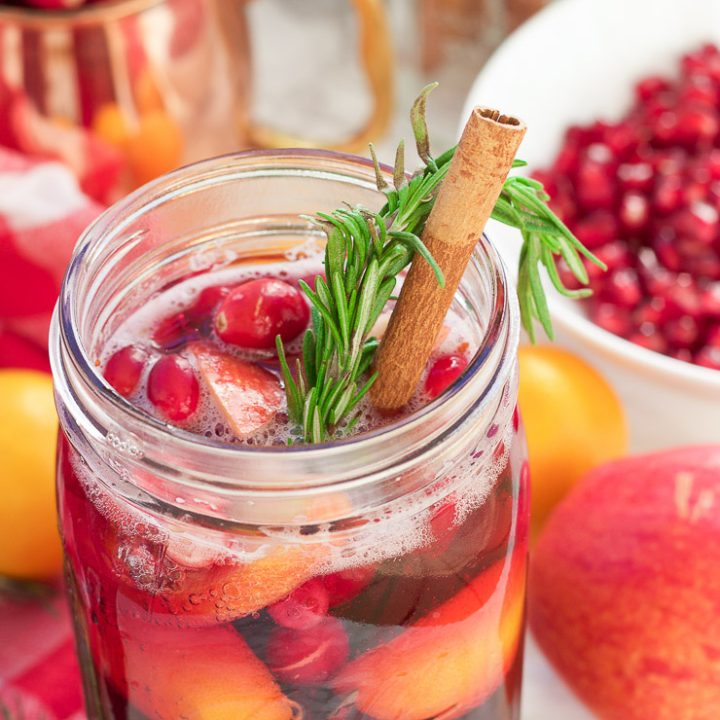 This winter pomegranate cranberry Christmas sangria recipe is a quick and easy twist on the popular sangria drink. Impress everyone at your next holiday or Christmas party with this sparkling red wine cocktail with apples, oranges, pomegranate, cranberry, rosemary, and cinnamon sticks! Get your drink on fancy pants!