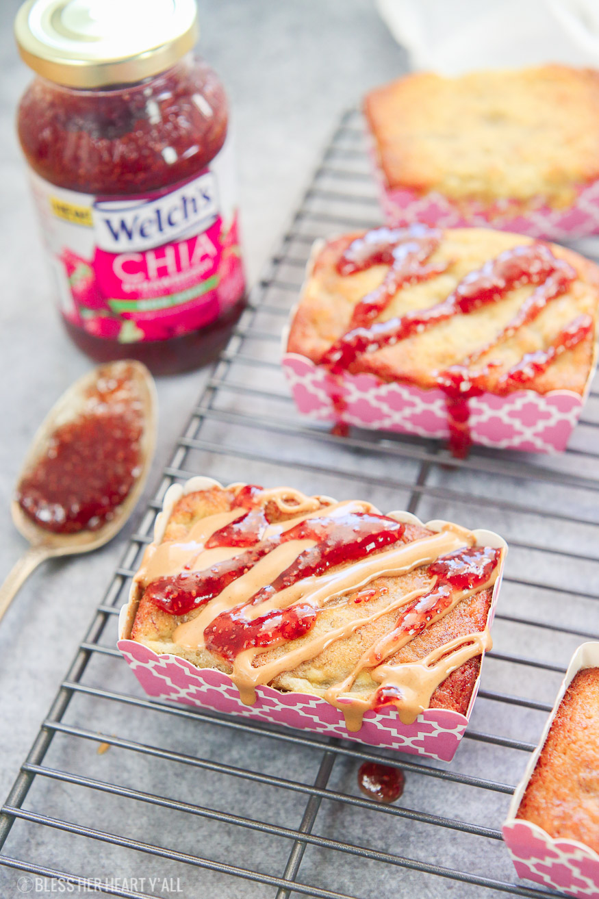 Moist gluten free mini peanut butter + jelly banana bread loaves are generously drizzled with Welch's Chia Strawberry Fruit Spread and all natural peanut butter for the perfect individualized breakfast!