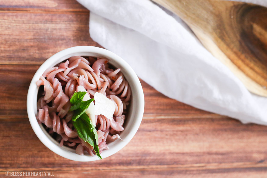 This gluten free red wine pasta + garlic basil goat cheese sauce is the perfect quick and fancy date night recipe that's ready in under 20 minutes! The pasta is cooked and stained in red wine and then tossed in a creamy garlic basil goat cheese sauce.