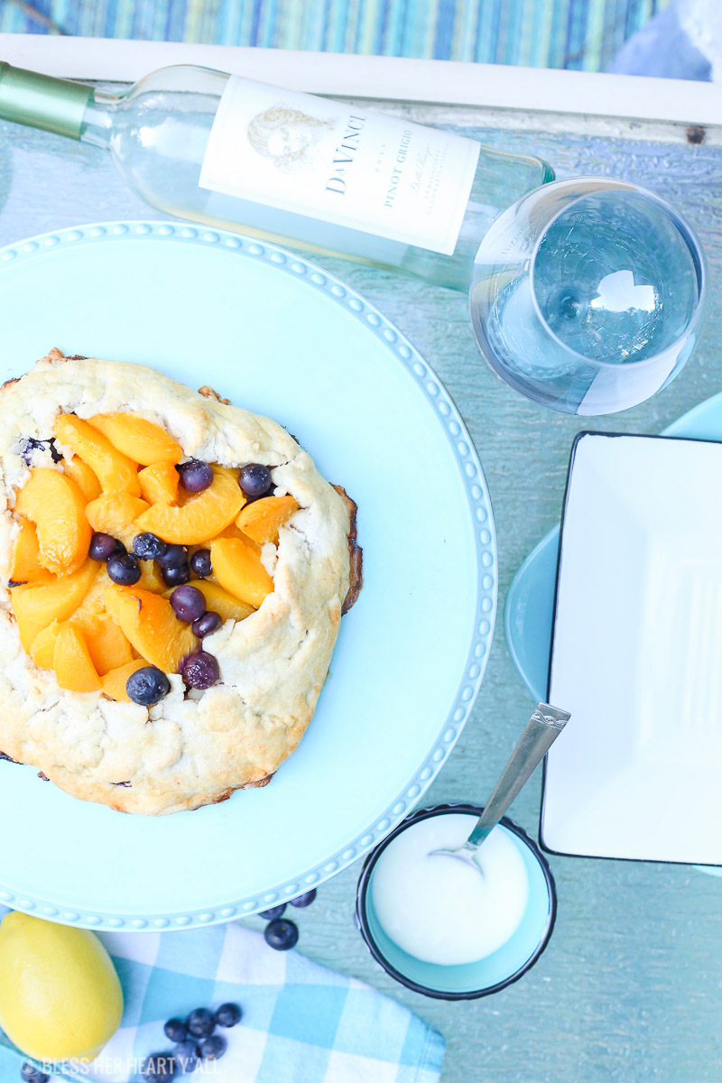 This peach blueberry galette combines peach slices and fresh blueberries in a sweet juicy sauce and then spreads it inside a doughy sugar-lined crust and bakes it all to golden perfection. This gluten free tart is drizzled in a light lemon glaze and is the perfect summer snack to enjoy outside on the back deck with a chilled bottle of white wine!