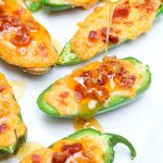 Pimento jalapeno poppers melt fresh jalapenos and pimento cheese together and then top them with crisp bacon crumbles and a drizzle of fresh honey. Each bite combines sweet and spicy with warm melty cheese and crunch. The perfect snack or appetizer in just 5 minutes! 1