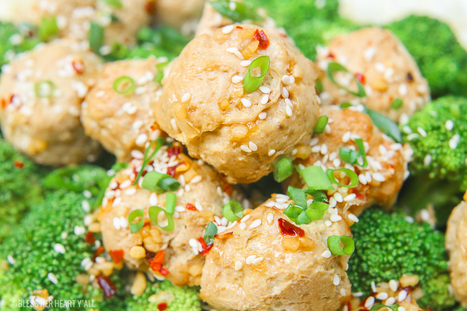 Sesame ginger paleo turkey meatballs bake soft paleo meatballs in a drizzle of homemade sweet and zesty sesame ginger sauce and topped with sesame seeds and green onion slivers. It's the perfect gluten-free, grain-free, and dairy-free appetizer or meal over rice and steamed vegetables! image 1