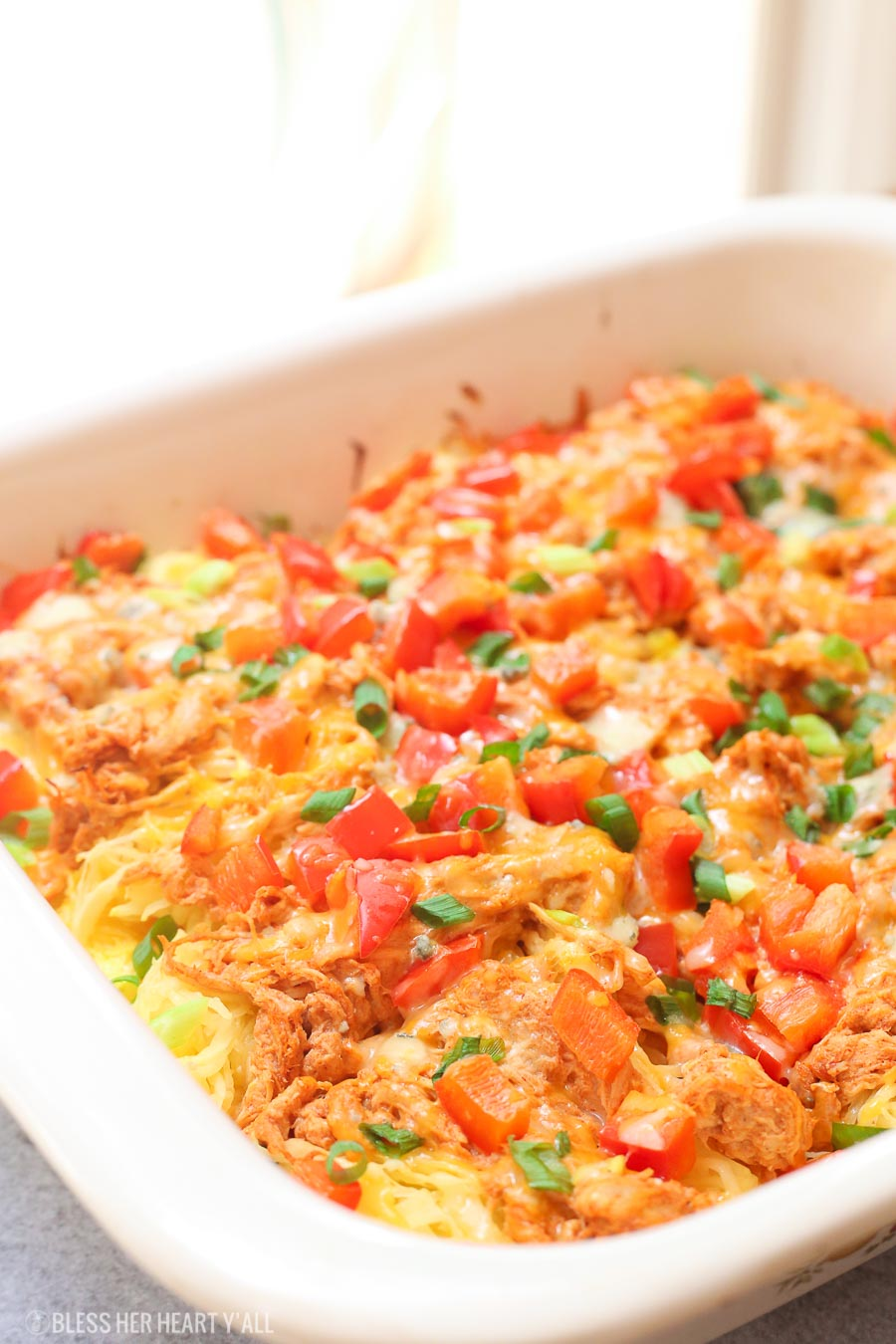 Skinny buffalo chicken spaghetti squash bake combines creamy flavor-packed buffalo chicken with fresh veggies and blue cheese crumbles all on a bed of spaghetti squash!