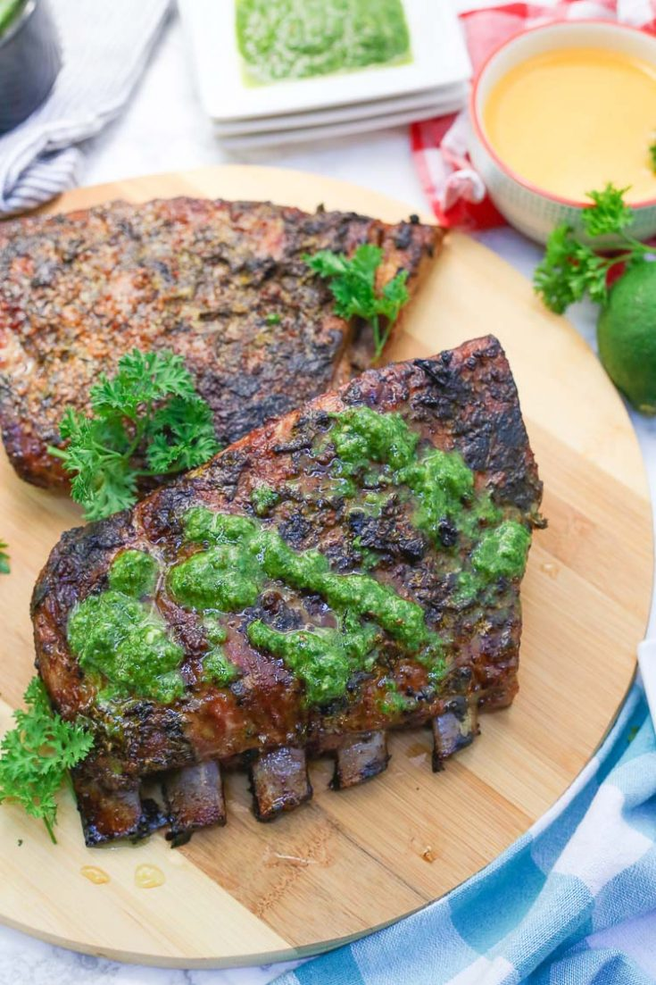 Cuban Mojo Marinated Pork Ribs are an amazing summer dish that combines tropical citrus flavors with savory cuban-inspired spices, and refreshing hints of mint, cilantro, and parsley to finish! The quick chimichurri drizzle adds an herbal garlicky kick to this grilled recipe! #grilling #grilled #chimichurri #mojo #ribs