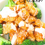 bang bang chicken is baked and not fried and is gluten-free with green broccoli florets in a white bowl with white creamy bang bang sauce drizzled on top