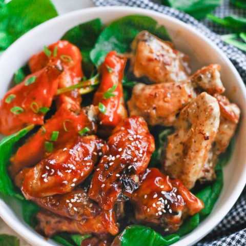 air fryer chicken wings with three different sauces in white bowl with vegetable greens