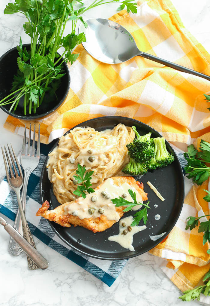 overhead shot of creamy instant pot chicken piccata with cream pasta in black plate with herbs