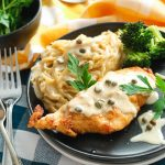 creamy instant pot chicken piccata that is gluten-free with pasta in black bowl with herbs