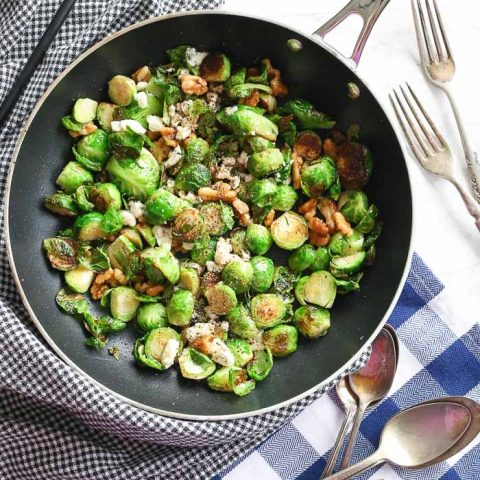 overhead view of brussel sprouts and walnuts in skillet pan